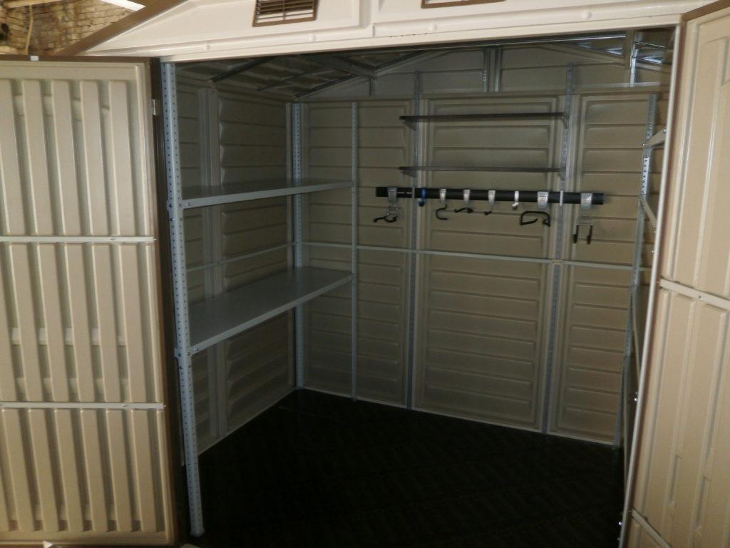 На фотографии показаны стеллажи в гаражной небольшой теплице