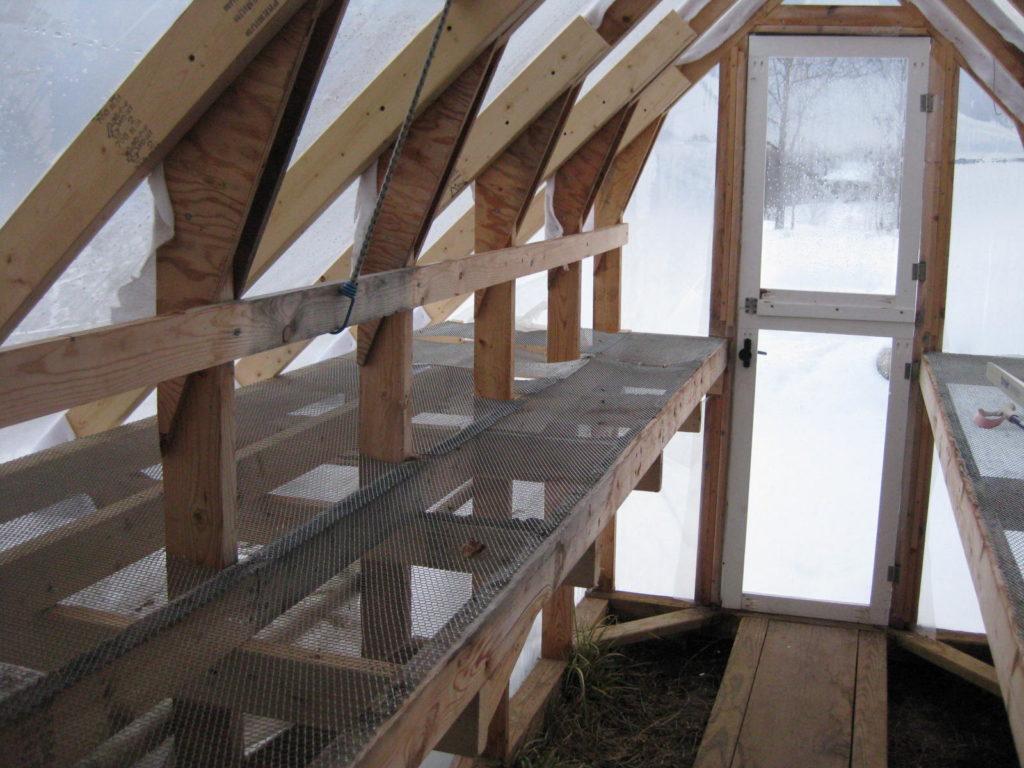 Мы видим пример небольшой домашней теплицы с деревянными стеллажами